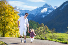 Engendrez avec le bébé sur la route entre les montagnes de neige Photographie stock