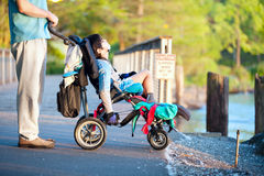 Engendrez avec le fils handicapé dans le fauteuil roulant au parc, appréciant le coucher du soleil images libres de droits