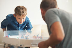 Engendrez avec le fils jouant avec enthousiasme avec l'hockey de table photo libre de droits