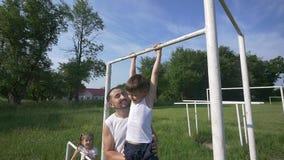 Engendrez avec le fils sur la formation de terrain de jeu, vraie famille heureuse souriant dehors, concept de personnes de mode d clips vidéos