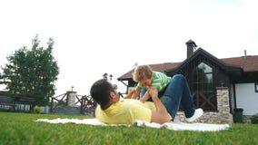 Engendrez avec son petit fils jouant dans l'herbe sur le parc d'été banque de vidéos