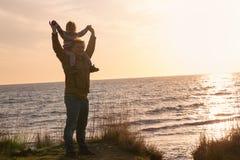 Engendrez avec un bébé au coucher du soleil par la mer Photographie stock