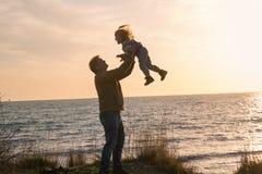 Engendrez avec un bébé au coucher du soleil par la mer Images stock