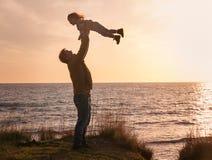 Engendrez avec un bébé au coucher du soleil par la mer Photos stock