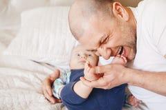engendrez dans le T-shirt blanc se situant dans le lit avec le fils nouveau-né de bébé embrassant en mordant ses orteils de pieds Photo stock