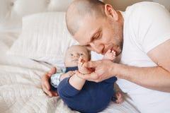 engendrez dans le T-shirt blanc se situant dans le lit avec le fils nouveau-né de bébé embrassant en mordant ses orteils de pieds Photographie stock libre de droits