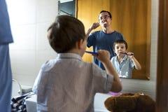 Engendrez en enseignant au fils comment se brosser les dents images stock