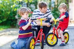 Engendrez enseigner deux garçons de petit enfant à réparer la chaîne sur des vélos Image libre de droits