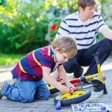 Engendrez enseigner deux garçons de petit enfant à réparer la chaîne sur des vélos Photos stock