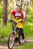 Engendrez enseigner sa fille à monter un vélo image stock