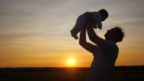 Engendrez entourer dans des bras de petit bébé au soleil de soirée de coucher du soleil banque de vidéos