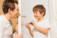 Engendrez et badinez le fils réparant la poignée de porte ensemble Image libre de droits