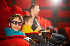 Engendrez et deux enfants, garçons, observant le film de bande dessinée dans le cin Photos libres de droits