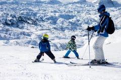 Engendrez et deux garçons, skiant un jour ensoleillé sur un sommet de montagne Photo stock