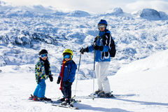 Engendrez et deux garçons, skiant un jour ensoleillé sur un sommet de montagne Image stock