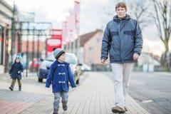 Engendrez et deux petits garçons d'enfant de mêmes parents marchant sur la rue en germe Photo stock