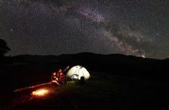 Engendrez et deux randonneurs d'enfants ayant un repos au camping en montagnes sous le ciel nocturne complètement des étoiles et  Images stock