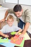 Engendrez et fils de sourire faisant les formes de papier ensemble à la table Photos stock