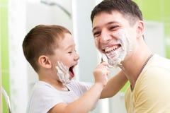 Engendrez et le sien fils d'enfant jouant dans la salle de bains Photo libre de droits