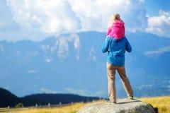 Engendrez et sa fille admirant une vue de stupéfier les montagnes rocheuses de dolomites de la province du sud du Tyrol de l'Ital Photo stock