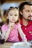 Engendrez et sa fille détendant en café extérieur Image stock