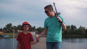 Engendrez et sa jeune pêche de fils le soir Images stock