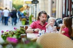 Engendrez et ses filles détendant en café extérieur Image stock