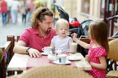 Engendrez et ses filles détendant en café extérieur Photo libre de droits