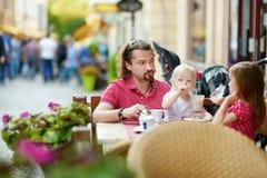 Engendrez et ses filles détendant en café extérieur Images libres de droits