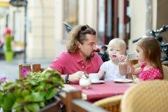 Engendrez et ses filles détendant en café extérieur Photos stock