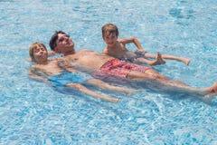 Engendrez et ses garçons s'étendant dans une piscine Photos stock
