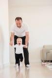 Engendrez et son beau bébé jouant et apprenant comment marcher Photos libres de droits