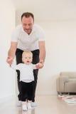 Engendrez et son beau bébé jouant et apprenant comment marcher Image libre de droits
