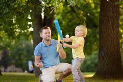 Engendrez et son fils jouant le base-ball en parc photos stock