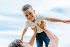 Engendrez jeter son petit fils dans le ciel temps de famille ensemble Petit garçon heureux ayant l'amusement avec son papa dehors Photos stock