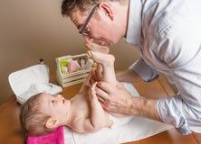 Engendrez jouer avec des pieds de bébé après couche-culotte de changement Photographie stock libre de droits