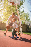 Engendrez jouer le basket-ball ensemble sur le cour de basket-ball Photo stock
