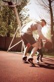 Engendrez jouer le basket-ball ensemble sur le cour de basket-ball Images stock