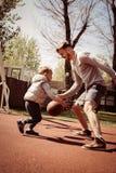 Engendrez jouer le basket-ball ensemble sur le cour de basket-ball Image libre de droits