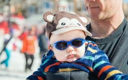 Engendrez juger le bébé habillé pour la chaleur dans le transporteur Photo libre de droits