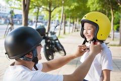 Engendrez l'essai de porter un casque de vélo à sa fille Photographie stock libre de droits