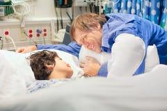 Engendrez l'observation au-dessus du fils handicapé dans le lit d'hôpital Images libres de droits
