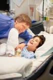 Engendrez l'observation au-dessus du fils handicapé dans le lit d'hôpital Photos stock