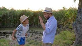 Engendrez la boxe de enseignement de fils à la nature, battements de petit garçon sur des mains de papa sur le coucher du soleil  banque de vidéos