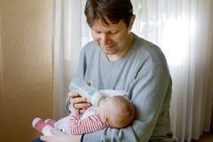 Engendrez la fille nouveau-née de alimentation de bébé avec du lait dans la bouteille de soins Photos stock