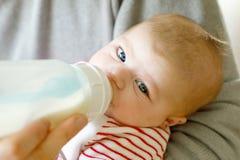 Engendrez la fille nouveau-née de alimentation de bébé avec du lait dans la bouteille de soins Photos libres de droits