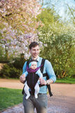 Engendrez la petite fille de transport avec le kangourou en parc Image libre de droits