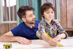 Engendrez le fils concentré de aide pour prendre des mesures de planche en bois dans l'atelier photo libre de droits