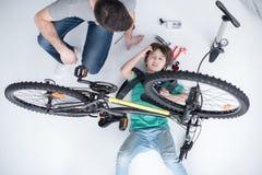 Engendrez le fils de aide avec des outils réparant la bicyclette sur le blanc Image stock