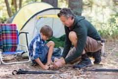 Engendrez le fils de aide pour porter des sandales par la tente Photo libre de droits